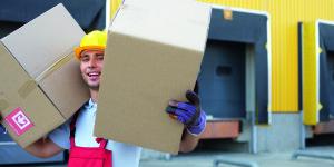 Lagerarbeiter traegt zwei Kartons auf den Schultern, Laderampen